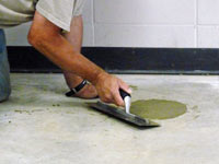 Repairing the cored holes in the concrete slab floor with fresh concrete and cleaning up the Darien home.