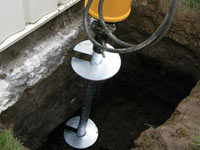 Installing a helical pier system in the earth around a foundation in Greenwich