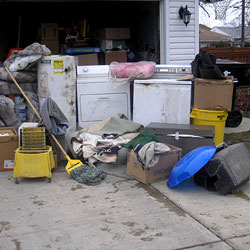 Soaked, wet personal items sitting in a driveway, including a washer and dryer in Milford.