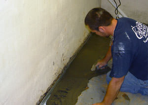 Restoring a concrete slab floor with fresh concrete after jackhammering it and installing a drain system in New Milford.