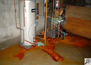 Puddles of reddish, brown, and yellow iron ochre flooding on a basement floor near some utilities.